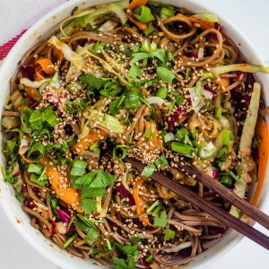 Soba noodle cold salad with peanut butter sauce in a white bowl with chopsticks