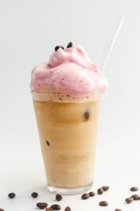 Pink vegan whipped coffee topping iced coffee latte in a glass cup