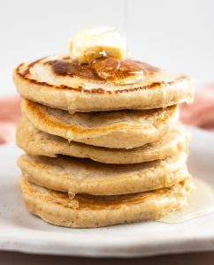 stack of pancakes made from flour and topped with butter and maple syrup on white plate