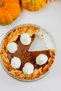 Pumpkin pie in the pie plate topped with coconut whipped cream