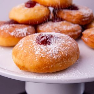 fried vegan doughnut filled with strawberry jelly on a white dish