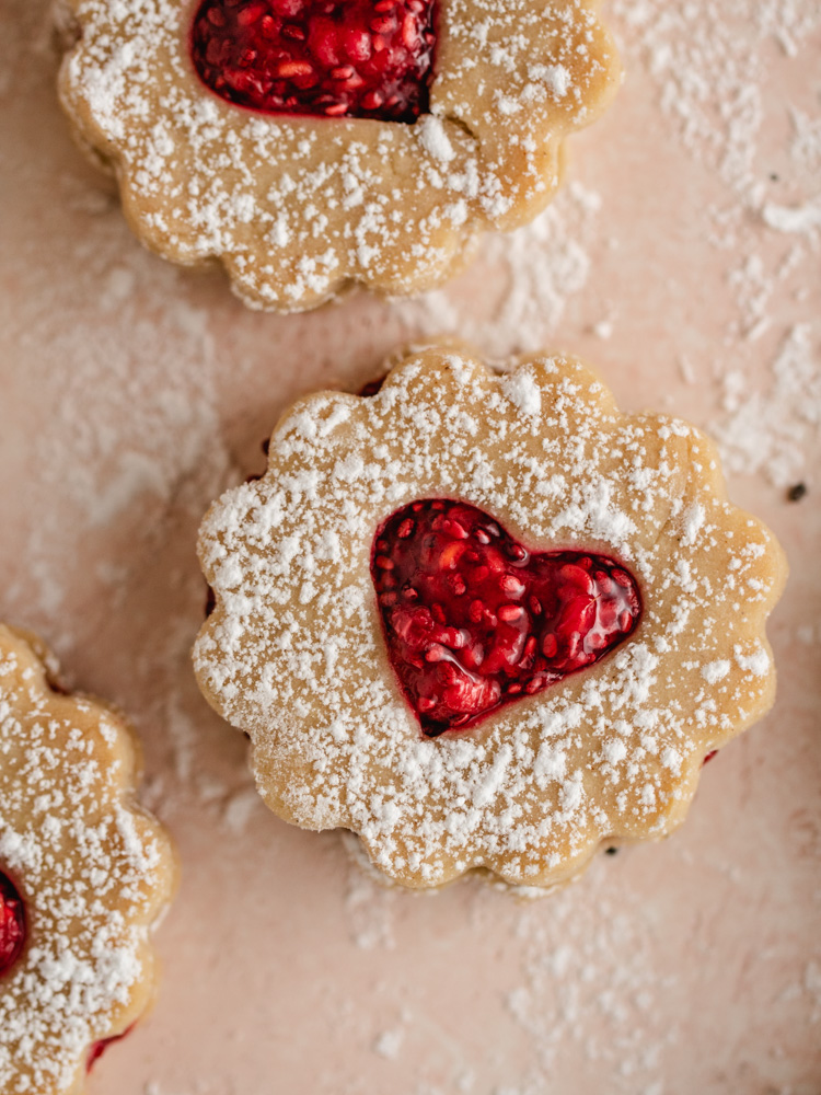 Vegan Almond Linzer Cookies heart shape with sugar flakes falling on top